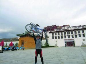 黄海星在布达拉宫前面奋力举起自己的自行车。