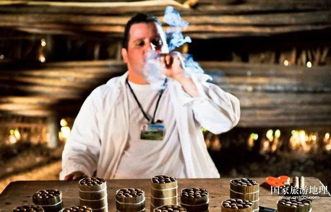 """古巴人每年吸2.5亿支雪茄烟,另有6500万支""""哈瓦那""""雪茄出口国外 F2.8,1/80秒,ISO2500 独特的烟叶混合法 为了让人们在享受雪茄时,有缝隙让烟通过,古巴雪茄的烟芯是采取人工手撕的方法,将烟叶纵向撕成两片,再进行烟芯的制作,这也正是手制雪茄才能拥有的特色。古巴雪茄的烟芯,是以下列三种烟叶所制成的,依不同比例混合后,便形成各品牌所独具的风味。而不同的烟叶制造出的雪茄味道也完全不同。 里格路烟叶(LIGERO) —— 虽然LIGERO字面直译为"""