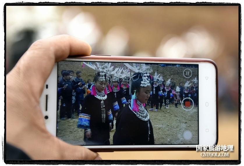 2018年3月31日,贵州省从江县苗族同胞相聚东朗镇举行踩歌堂活动。图为:小伙子用手机录制苗族女孩芦笙舞(龙梦前摄)