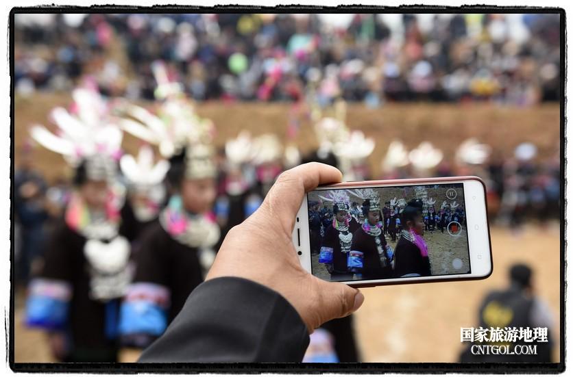 2018年3月31日,贵州省从江县苗族同胞相聚东朗镇举行踩歌堂活动。图为:小伙子用手机录制苗族女孩芦笙舞2(龙梦前摄)