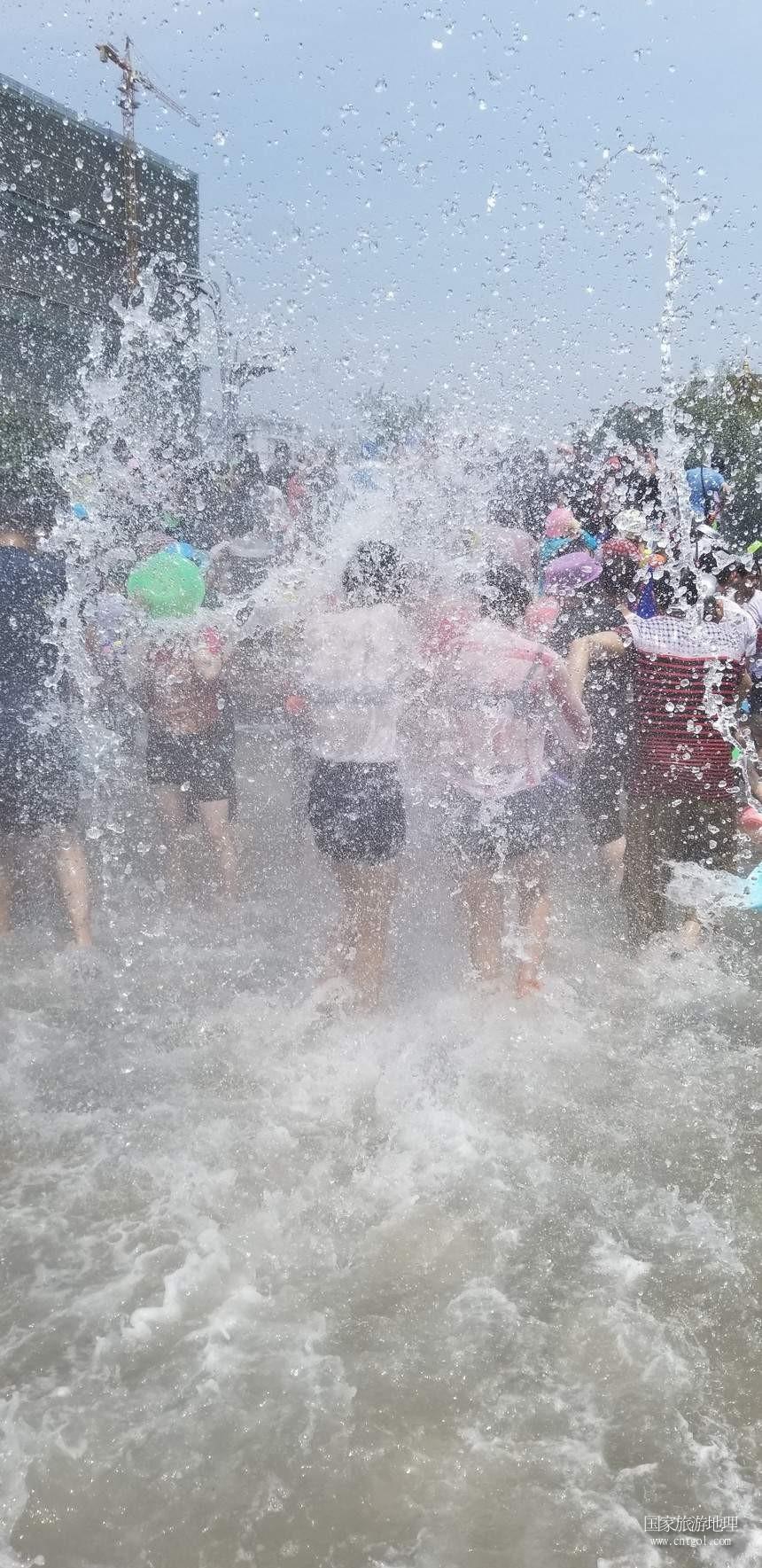 今天(4月15日),一年一度的泼水节泼水活动在云南西双版纳傣族自治州景洪市举行,吸引了数万民当地居民和游客参与。据悉,当地各县市乡村群众也自发在当地进行了这一传达吉祥如意、饱含对亲友祝福的泼水活动,几乎万人空巷,全民参与。这是民众在设于景洪市区泼水活动现场欢快泼水,。