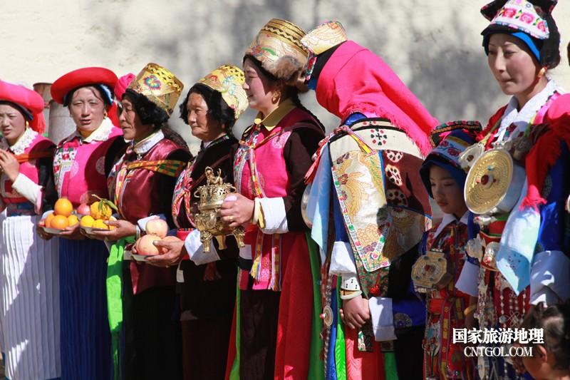 接亲现场,娘家人背着水等待迎接,新娘则带着面巾害羞地靠在母亲身边。