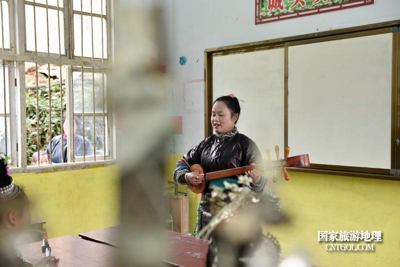 贵州省黔东南苗族侗族自治州从江县往洞镇增盈小学杨秀美老师对学生进行琵琶弹奏示范教学。摄影 龙梦前