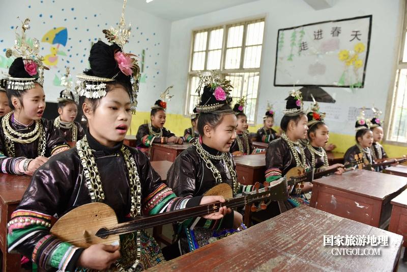 贵州省黔东南苗族侗族自治州从江县往洞镇增盈小学学生一边弹奏琵琶一边唱琵琶歌。摄影 龙梦前