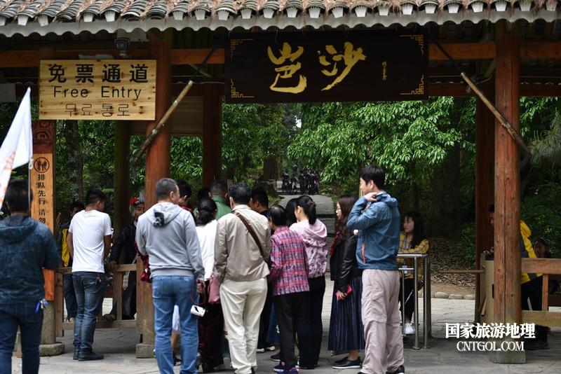 游客在贵州省黔东南苗族侗族自治州从江县岜沙原生态苗族文化旅游区门口检票。