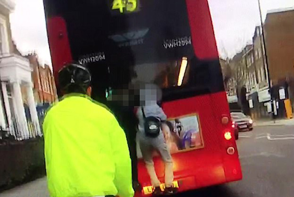 危险!英国两少年攀附行驶巴士尾部引热议